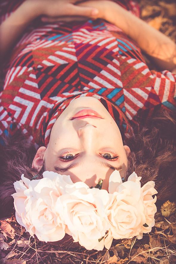 ילדה עם שמלה אדומה וזר ורדים ורוד