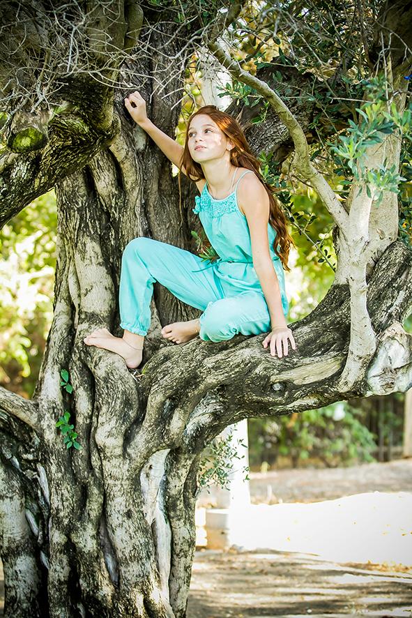 בוק בת מצווה בטבע- ילדה עם אוברול כחול על עץ זית