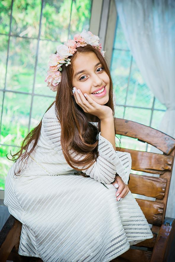 ילדה עם שמלה לבנה על כסא מעץ