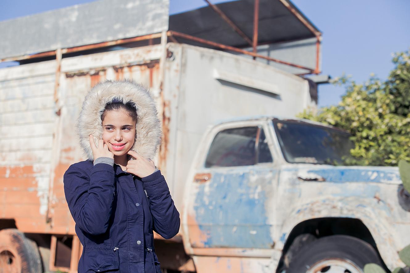 ילדה עם מעיל כחול רקע משאית- צילומי בת מצווה בכפר