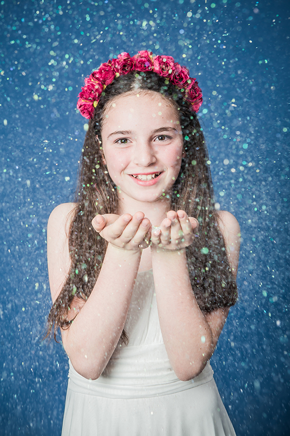 צילום בת מצווה ילדה מעיפה קונפטי רקע כחול