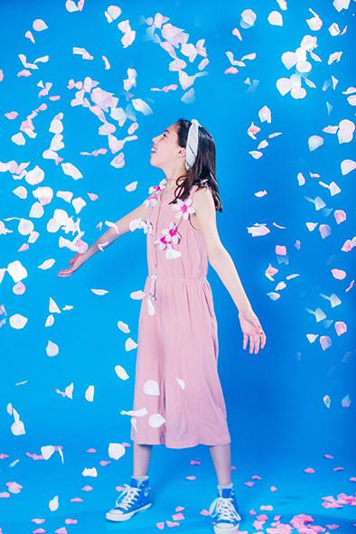 צילום בת מצווה ילדה באוברול ורוד ועלי כותרת מעופפים