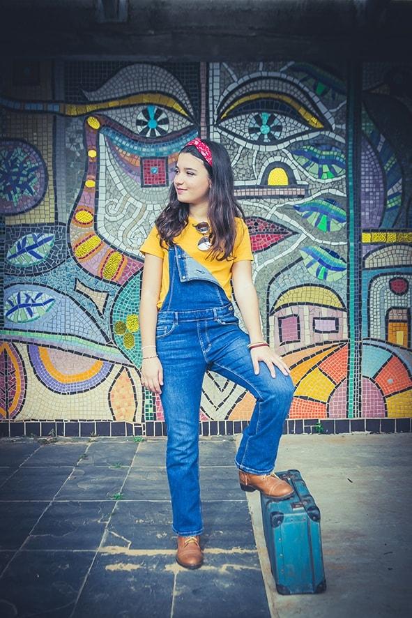 ילדה עומדת על מזוודה כחולה